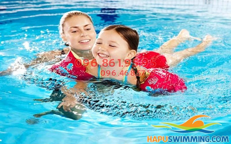 Bé học bơi cùng giáo viên nữ tại bể bơi Hapulico